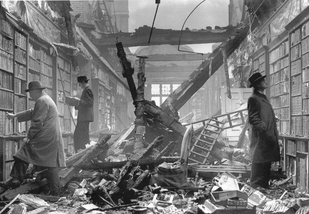A library with the ceiling caved in. Beams, rubble, curtains, and ladders are heaped in the center. Three men in hats and wool coats inspect the books that remain on the shelves.