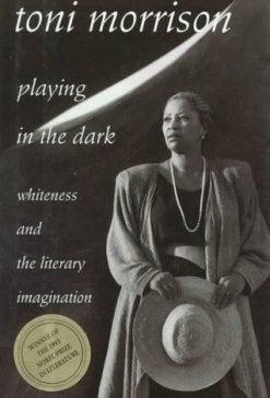 : The greyscale cover of Toni Morrison's book Playing in the Dark. Morrison holds a giant floppy hat. A gold sticker proclaims that the book won the 1993 Nobel Prize in Literature.