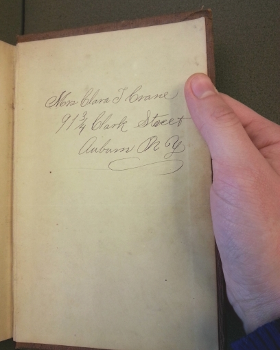 A hand holds open the back cover of a book, with Mrs Clara T Crane's name and address written in large, curly script.