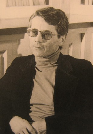 A sepia-toned portrait photograph of a middle-aged white man in a turtleneck, corduroy blazer, and tinted glasses.