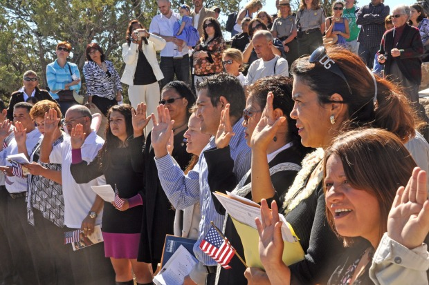 A row of people with their right hands raised; some hold documents and small American flags in their left hands; spectators crowd on the steps behind them.